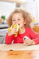 Adorable girl eating banana.