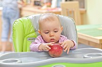 Baby girl sitting a high chair, playing with apple.