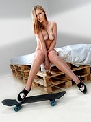 Young, naked woman sitting on a pallet with a skateboard.