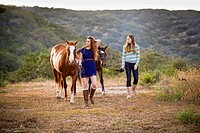 USA, Texas, Sisters walking with Quarterhorses near mountain