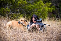 Young woman with hunting rifle besides blackmouth cur dog