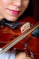 Young woman playing violin, smiling