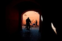 Man riding a bicycle and passing through a passage in Marrakech medina, Morocco