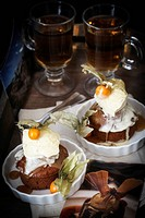 Sticky toffee pudding with vanilla ice cream, physalis and tea in background