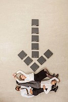 Business people lying below down arrow sign formed by files