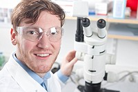 Germany, Portrait of young scientist with microscope in laboratory, smiling