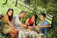 Austria, Salzburg Country, Family dining in garden, smiling