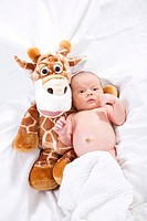 Baby lying with giraffe doll on bed