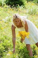 Austria, Altenmarkt-Zauchensee, Mid adult woman in alpine meadow with arnica