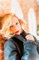 Portrait of a 34 year old blond woman wearing a leather jacket looking at the camera
