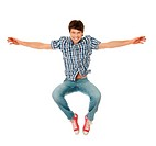 Happy young man jumping, wearing plaid jeans and red sneakers.