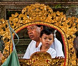 A BALINESE father and son are dressed traditionally at PURA BEJI in the village of Mas during the GALUNGAN FESTIVAL , Indonesia, Bali, Ubud