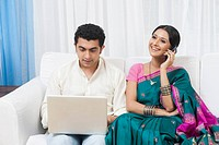 Man using a laptop with his wife talking on the mobile phone beside him