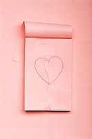 Notepad with hand drawn heart ripped and mended with scotch tape