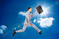 Happy businessman jumping with his briefcase