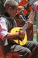 canarian guitarist seated playing the bandurria or lute-type instrument accompanied by a man standing playing the spanish guitar