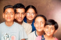South Asian Indian family with four brother and one sister looking to the camera with smile