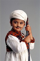 Young Gujarati boy dressed as an adult farmer, wearing a kedyu with a false moustache , holding a stick
