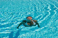 Woman swimming to surface of pool