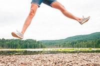 A woman jumping beside a lake in Bowen Island, British Columbia, Canada.