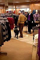 Elderly man training a young service dog in a shopping mall department store