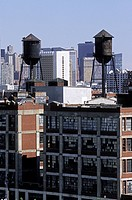 Water towers sit on an abandoned factory in downtown with high rises in the background, Jersey City, Hudson County, New Jersey