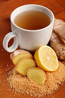 Cup of ginger tea and fresh ingredients - ginger, lemon and brown sugar.