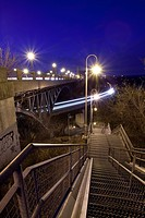 A steel stairwell leading down under a bridge with a train passing by in Hamilton, Ontario, Canada.