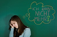 Depressed looking teacher standing in front of the blackboard with a speech bubble, Ich kann nicht mehr, German for I can't take anymore, symbolic ima...