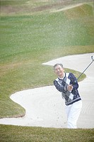 middle aged man doing bunker shot at golf course