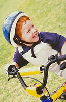 portrait, redheaded boy with freckels, 6 years, wearing blue helmet rides laughing his yellow GMX bike over green grassland  - GERMANY, 27/01/2004