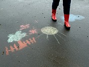 MR legs of a person woman with red rubberboots going for a walk in rainy weather on a wet road with black asphalt surface with a drawing of children k...