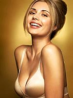 Portrait of a beautiful young happy smiling woman wearing a bra in golden colors isolated on shiny gold background.