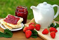 Mug, toast, glass with strawberry jam and strawberries.