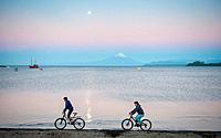 Two Cyclists on Beach, Puerto Varas, Chile.