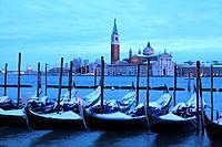 Snow covered gondolas at dawn, San Giorgio Maggiore, Venice, Italy.