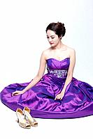 a lady in fancy purple dress sitting on the floor gracefully
