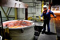 Germany, Essen, 121.09.2012 The Trimet Aluminium AG, Essen is Germany's largest aluminum producer. Photo: A worker removes slag from the molten alumin...