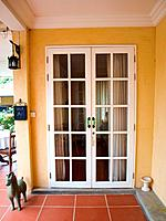 Double patio white french doors with windows on yellow wall.