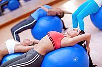 Hispanic women using exercise balls in gym