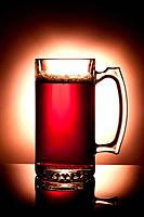 A studio image of a large mug of beer that is back lit.