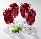 Summer fruit pudding, containing mixed berries and bread which is coloured from the fruit juices, served in four clear glasses