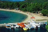 Greece, Skiathos, sweeping bay of Koukounaries, with sunbathers, and boats moored in a small harbour area, wooded area behind.