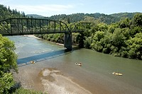 USA, California, people canoeing on Russian River near Guerneville Bridge