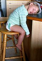 A two-year-old boy, sits up, fast asleep waiting for his supper ...