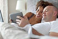 Married couple sharing tablet computer in bed.