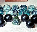 Glass gaming pieces found at Birka, Sweden. Semi-spherical glass gaming pieces and a 'king' of green glass with blue eyes, nose and crown.The latter i...