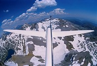 Glider plane Twin Astir flying close to Pena Collarada mountains with on left Ibon de Ip , Aragon, Spain.