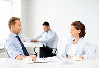 smiling businesswoman and businessman discussing something in office