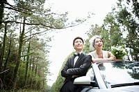 newlyweds next to convertible car